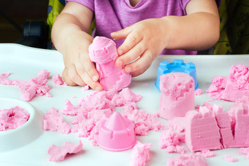 Childs hands building castle from kinetic sand on the table