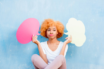 Beautiful african woman holding colorful thoughtful bubbles on the blue wall background
