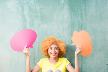 Beautiful african woman holding colorful thoughtful bubbles on the green wall background