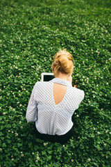 Woman with her computer sitting on the grass