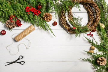 Make a Christmas wreath with your own hands. Spruce branch, Christmas wreath and gifts on a white wooden background