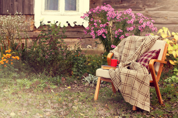 comfortable place to rest/ old chair with blanket, book and red mug stands in the garden near village house