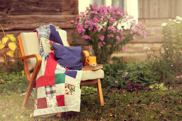 cozy autumn weekend/ old chair with a blanket, a book and a yellow mug stands in the garden near the wooden house