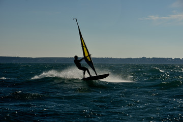silhouettte of a man windsurfing