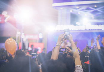 Asian  women holding smart phone and tapping screen for taking pictures on Crowd at concert stage lights,blurry background
