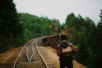 young man walks across train trestle