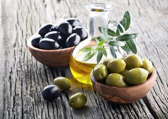 Olive oil and olives on wooden board
