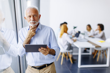 Senior businessman standing by window with digital tablet in his hand