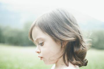 Close up of a cute little girl in a field