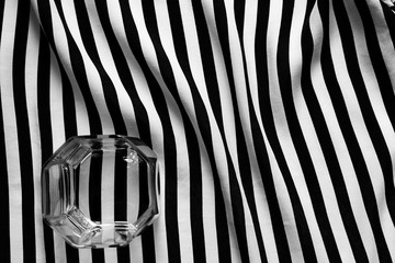 Black and white photo of a glass of old fashioned on a geometric background of lines