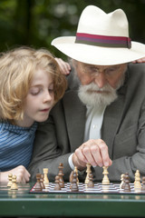 grandfather playing chess with his grandchildren