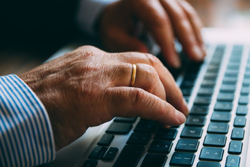 Detail of the hands of a senior businessman typing on a laptop keyboard