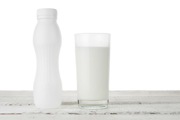 Milk glass and bottle on white background