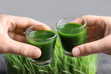 Hands of young men with shots of wheat grass juice