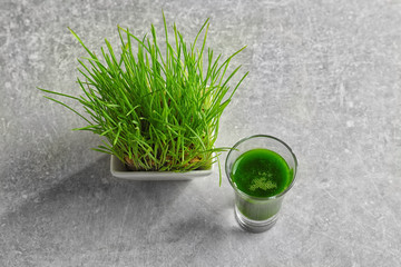 Sprouted wheat and shot of healthy grass juice on table
