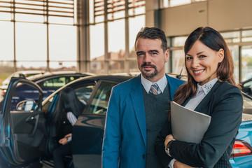 Portrait of two car sales consultant in car salon.