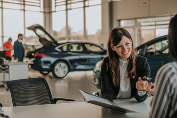Cheerful car dealer showing files and giving keys to client.
