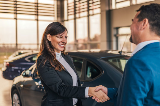 Cheerful car dealer handshake with customer in showroom.