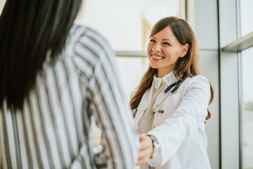 Female doctor talking and touching woman patient for encouragement.