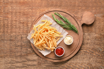Composition with yummy french fries on wooden background