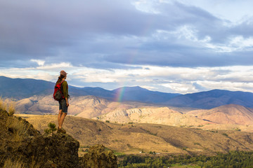 Woman stands on a cliff edge looking out at the mountainous scenery of the Methow Valley, WA