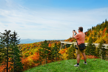 Man standing on top of the mountain taking photos ,looking at beautiful autumn mountains landscape foliage. Linn Cove Viaduct,  Blue Ridge Parkway. Copy space. North Carolina, USA.