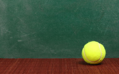 Tennis ball on desk, chalkboard background