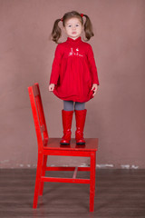 Pretty girl with brunnete hair stylish dressed red long shirt dress with cornrow happyly smiling posing camera photosession in modern showroom studio wearing baby boots sitting standing on chair.