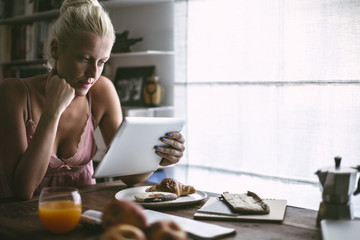 Blonde Caucasian Woman Reading From Her Tablet in the Morning
