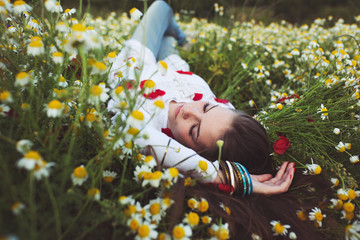 Beautiful young girl lying in meadow
