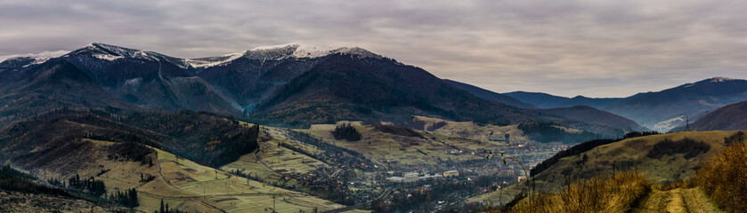 panorama of mountainous countryside in late autumn. great Borzhava mountain ridge with snowy tops and villge down the valley at sunrise