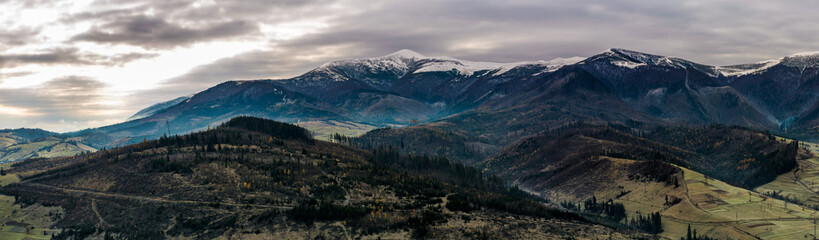 panorama of mountainous countryside in late autumn. great Borzhava mountain ridge with snowy Velykyi Verkh peak at sunrise