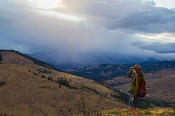 Woman stands looking out into the mountainous landscape of the Methow Valley in Washington State