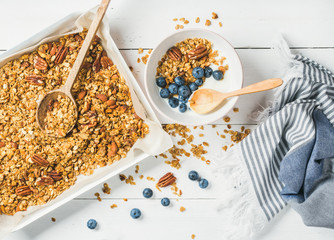 Healthy breakfast. Oat granola with pecan nuts, yogurt and blueberry in bowl on white wooden background, top view