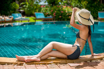 Women wearing bikini or swimware suits at swimming pool at the resort of Pattaya in Thailand.