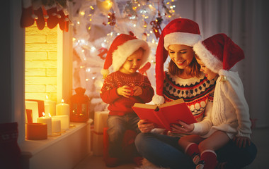 family mother and children read a book at christmas near   fireplace at home.