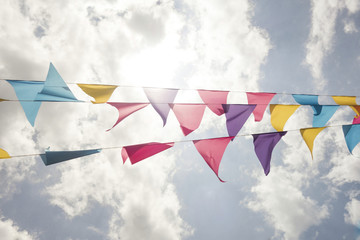 Colorful Triangle Banner Flags Waving in the Wind with Cloud Background