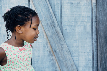 Profile of an African-American Girl in a Dress By A Wooden Shack