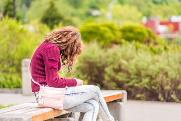 One young happy woman sitting on bench on sidewalk in green downtown city park in Saguenay, Canada, Quebec during summer looking at phone or reading book