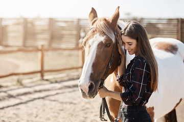 Young woman preparing to become a riding instructor taking care and talking to a horse on a hot autumn day.