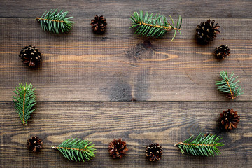 Spruce branch and pinecone pattern on wooden background top view copyspace