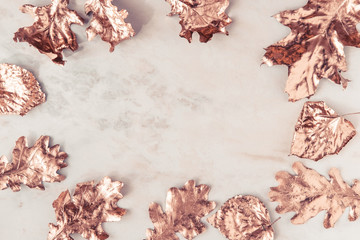 Frame made of fall rose gold colored leaves, creative flatlay on white marble background. Copy space for text