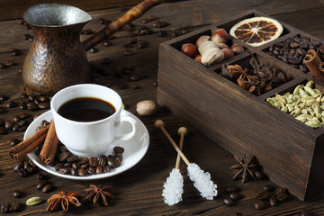 Black coffee in a white cup and various spices