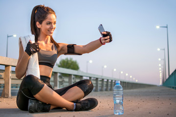 Smiling sporty girl taking a self portrait on phone after night workout.