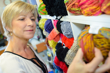 mature smiling blonde woman customer choosing multicolored spool with thread