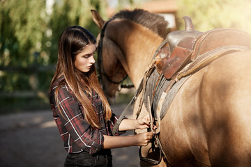Young woman preparing to ride a horse tying down the saddle.