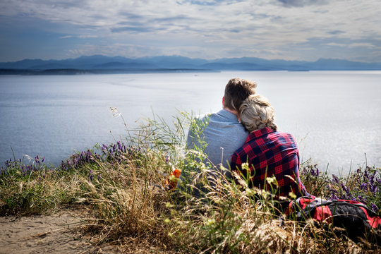Rear view of young couple sitting together on lakeshore