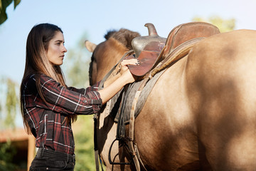 Female horse trainer preparing the saddle to have a ride on a ranch on a sunny autumn day dreaming about prairies