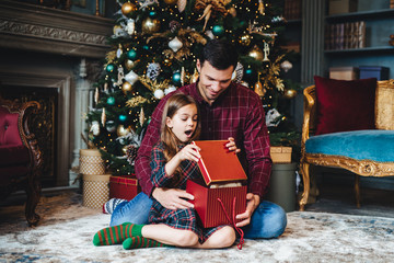 Surprised adorable small girl looks into present box, doesn`t believe her eyes, recieves pleasant gift from father, sit together on floor in cozy room near decorated New Year tree. Majestic momemt