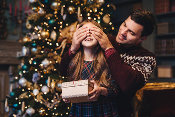 Portrait of young father covers his daughter`s eyes as going to make surprise for her, gives present, stand together near Christmas tree. Happy smiling girl recieves gift from dad. Surprise concept
